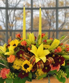 Adorn your Thanksgiving table with this centerpiece or send as a hostess gift. This centerpiece includes sunflowers, lilies, and orange spray roses.