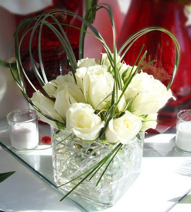 This year send luxury in a clear cube vase filled with winter white roses and artistic greenery.
